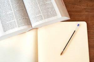 ספר משפטים פתוח עם מחברת ועט